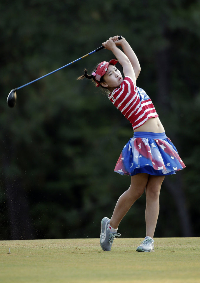 Photo - Lucy Li watches her tee shot on the 10th hole during the first round of the U.S. Women's Open golf tournament in Pinehurst, N.C., Thursday, June 19, 2014. (AP Photo/Chuck Burton)