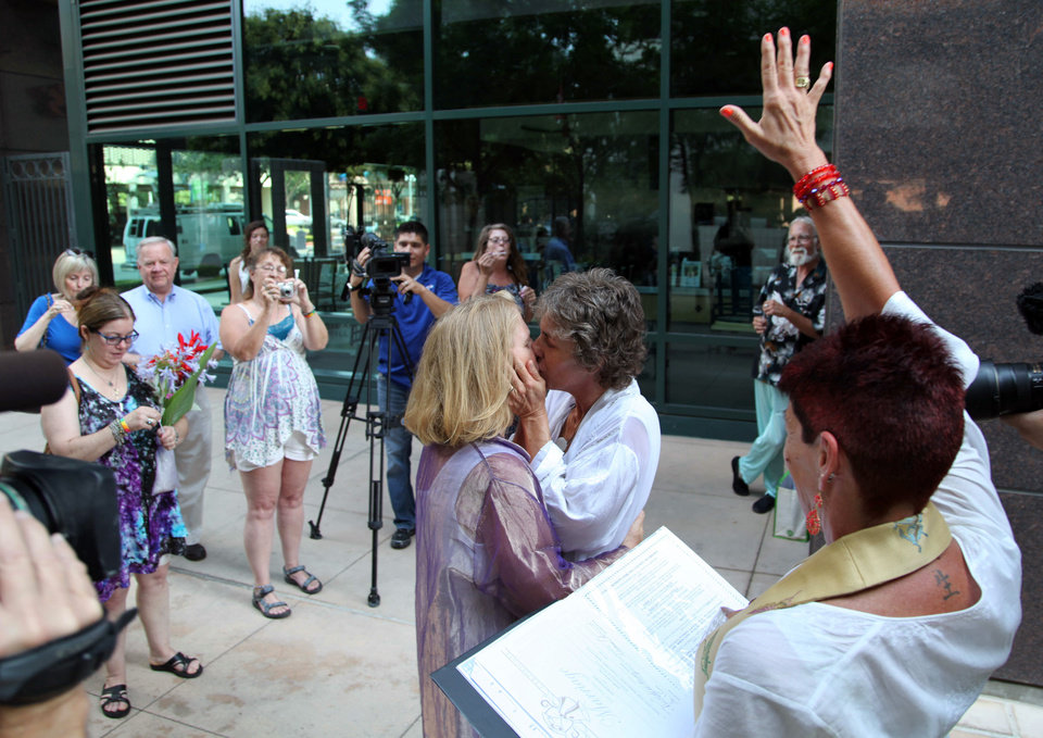 Photo - Naomi Hendrix, right, and Rio Waller kiss right after taking their wedding vows and being pronounced married in a small garden across from the Fresno County Clerk's office on Monday, June 1, 2013 . The women, who have been together for 16 years, got engaged on Wednesday, the day the Supreme Court struck down  the Defense of Marriage Act. (AP Photo/Gosia Wozniacka)