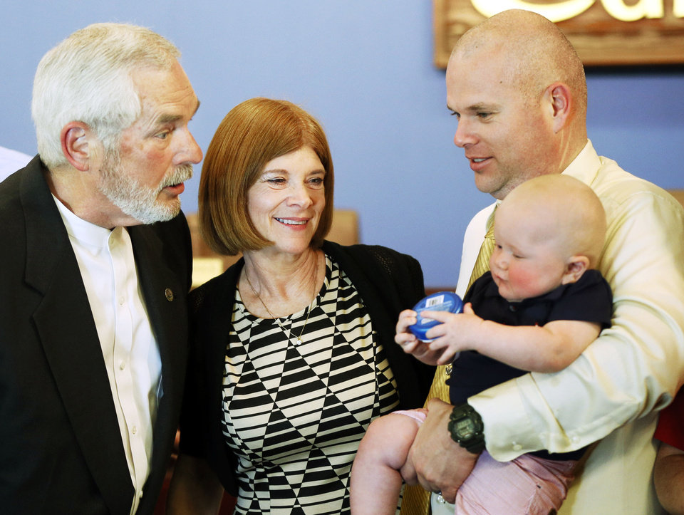 Photo - Edmond Mayor Charles Lamb, left, talks to his 6-month-old grandson, Grayson Lamb, held by son, Erik Lamb, as his wife, Cheri, looks on after Lamb took the oath of office. PHOTO BY NATE BILLINGS, THE OKLAHOMAN.   NATE BILLINGS - THE OKLAHOMAN