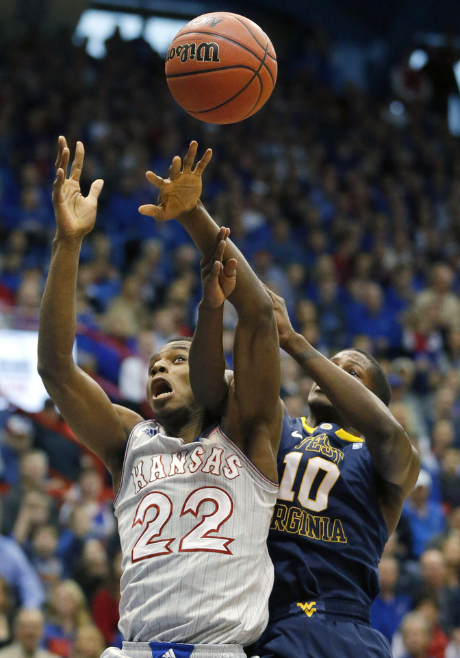 Photo - Kansas guard Andrew Wiggins (22) rebounds against West Virginia guard Eron Harris (10) during the first half of an NCAA college basketball game in Lawrence, Kan., Saturday, Feb. 8, 2014. (AP Photo/Orlin Wagner)