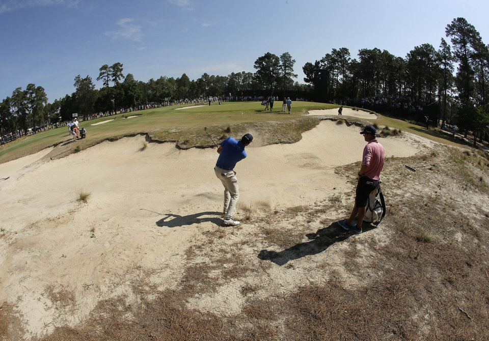 Photo - In this image made with a fish-eye lens, Matt Kuchar hits out of the bunker on the 12th hole during a practice round for the U.S. Open golf tournament in Pinehurst, N.C., Wednesday, June 11, 2014. The tournament starts Thursday. (AP Photo/Charlie Riedel)