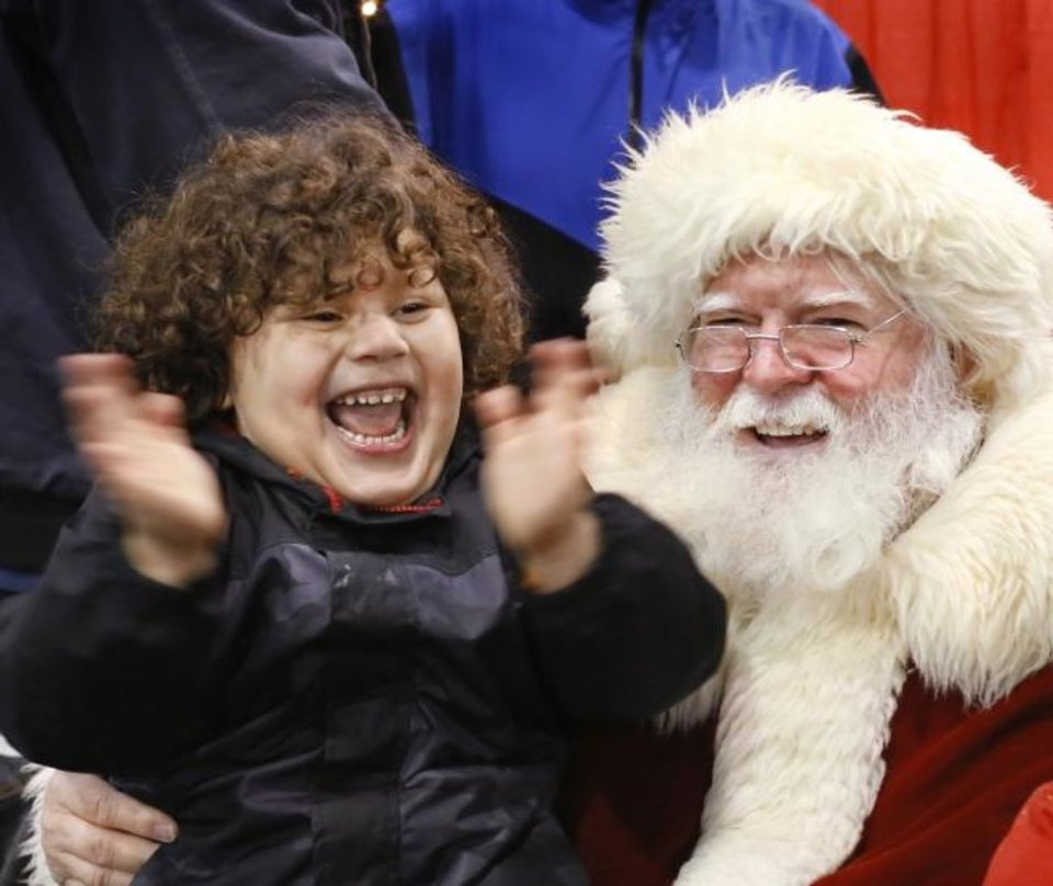 Photo -  After standing in line and eyeing the jolly man in the red suit and long white beard, Abel Hernandez, 4, was so excited when he jumped onto Santa's knee, a big smile covered his face and he screamed with joy, clapping his hands with happiness at the 72nd annual Red Andrews Christmas dinner at the Cox Convention Center on Dec. 25, 2018. [The Oklahoman Archives]