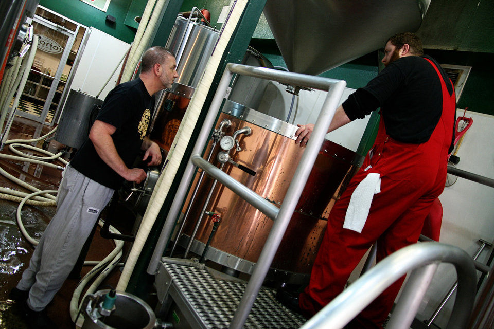 Choc Brewmaster Michael Lalli, left, consults with brewer B.J. Howell during a brew session for Gratzer beer. PHOTO BY NICK TROUGAKOS, THE OKLAHOMAN