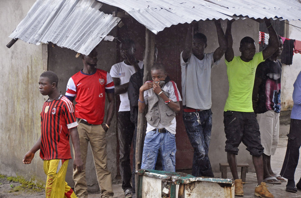 Photo - Family members and friends of a man believed to have died form the Ebola virus, gather near his home as his body is removed by health workers in Monrovia, Liberia, Friday, Aug. 29, 2014.  The Ebola outbreak in West Africa eventually could exceed 20,000 cases, more than six times as many as are now known, the World Health Organization said Thursday. A new plan released by the U.N. health agency to stop Ebola also assumes that the actual number of cases in many hard-hit areas may be two to four times higher than currently reported.(AP Photo/Abbas Dulleh)