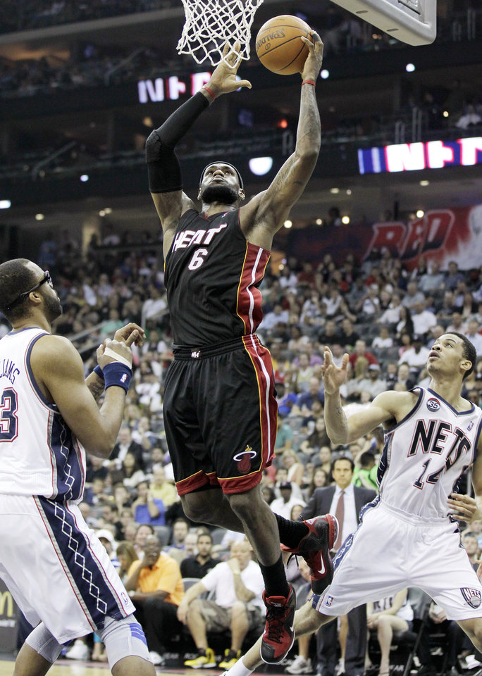Miami Heat's LeBron James (6) goes up for a shot against New Jersey Nets' Shelden Williams, left, and Gerald Green (14) in the first quarter of an NBA basketball game, Monday, April 16, 2012, in Newark, N.J. (AP Photo/Julio Cortez)