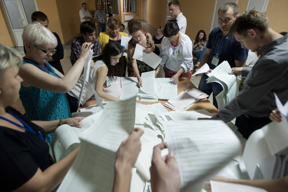Photo - Election commission officials count ballots at a polling station in Kiev, Ukraine, on Sunday, May 25, 2014. Ukraine's critical presidential election went underway Sunday under the wary scrutiny of a world eager for stability in a country. An exit poll showed that billionaire candy-maker Petro Poroshenko won election in the first round. (AP Photo/Evgeniy Maloletka)