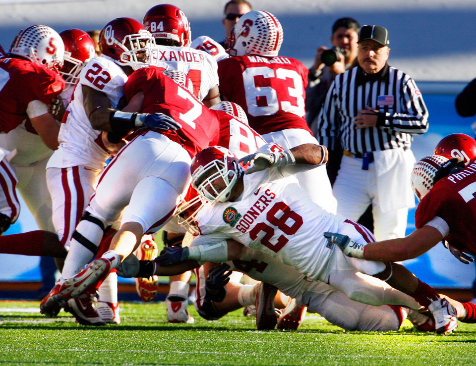 Photo - Keenan Clayton (22) and Travis Lewis (28) combine to stop Toby Gerhart on Stanford's last scoring threat during the 31-27 victory at the Brut Sun Bowl college football game between the University of Oklahoma Sooners (OU) and the Stanford University Cardinal on Thursday, Dec. 31, 2009, in El Paso, Tex.   Photo by Steve Sisney, The Oklahoman