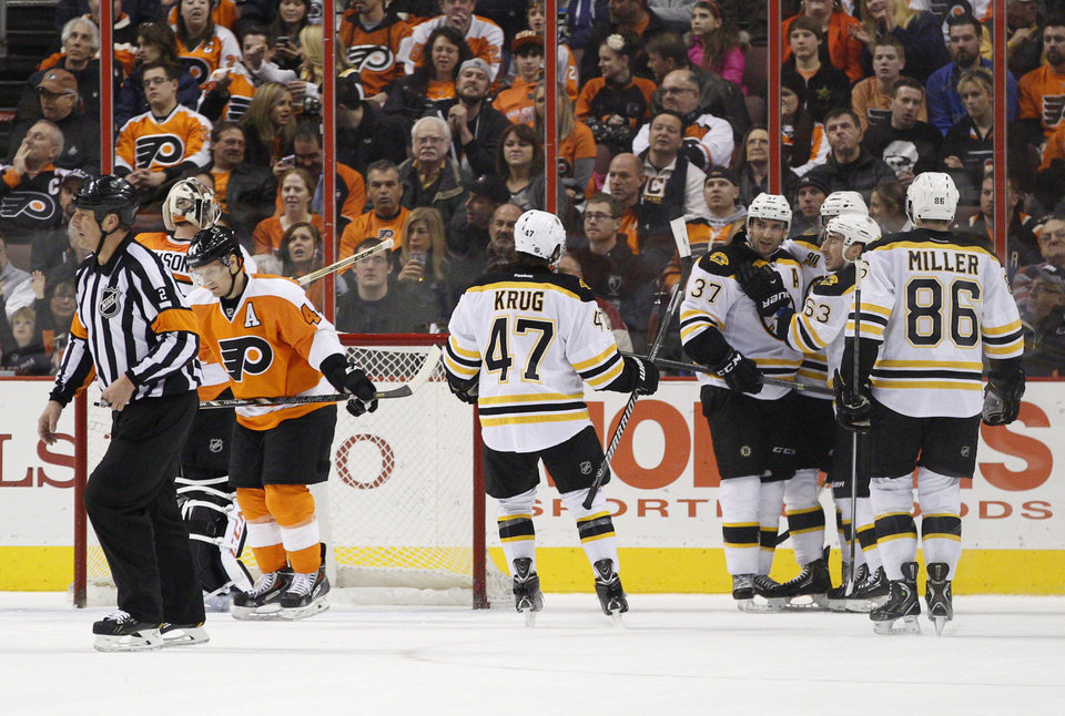 Photo - Boston Bruins' Patrice Bergeron, fourth from the right, celebrates his goal with teammates as Philadelphia Flyers' Steve Mason, second from the left, looks back with Kimmo Timonen, third from the right, of Finland, beside him during the second period of an NHL hockey game, Saturday, Jan. 25, 2014, in Philadelphia.  (AP Photo/Chris Szagola)