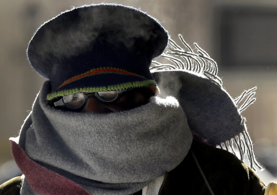 Photo - Jerome Harris is bundled up against the weather as wind blows up his scarf Monday, Jan. 6, 2014, in St. Louis. After the area was blanketed by snow on Sunday, dangerous cold settled across Missouri on Monday amid warnings that even a few minutes of exposure for people and pets could be deadly. (AP Photo/Jeff Roberson)