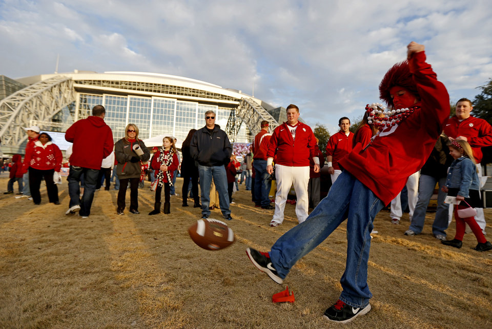 Photo - Dalton Denney, 10, of Clinton, Okla., kicks a football outside Cowboys Stadium before the Cotton Bowl college football game between the University of Oklahoma (OU)and Texas A&M University at Cowboys Stadium in Arlington, Texas, Friday, Jan. 4, 2013. Photo by Bryan Terry, The Oklahoman