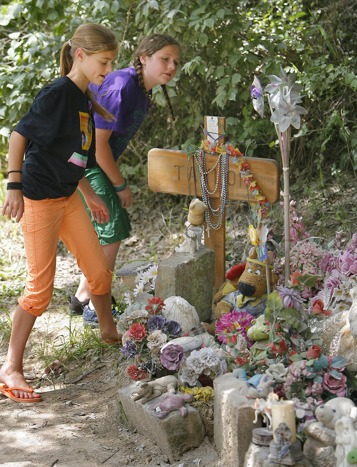 Photo - Destiny Smith, 12, and Stormie Morgan, 11, look over the memorial for their friends Skyla Whitaker and Taylor Placker Monday, June 8, 2009, on the one-year anniversary of their murders near Weleetka. Photo By David McDaniel, The Oklahoman.