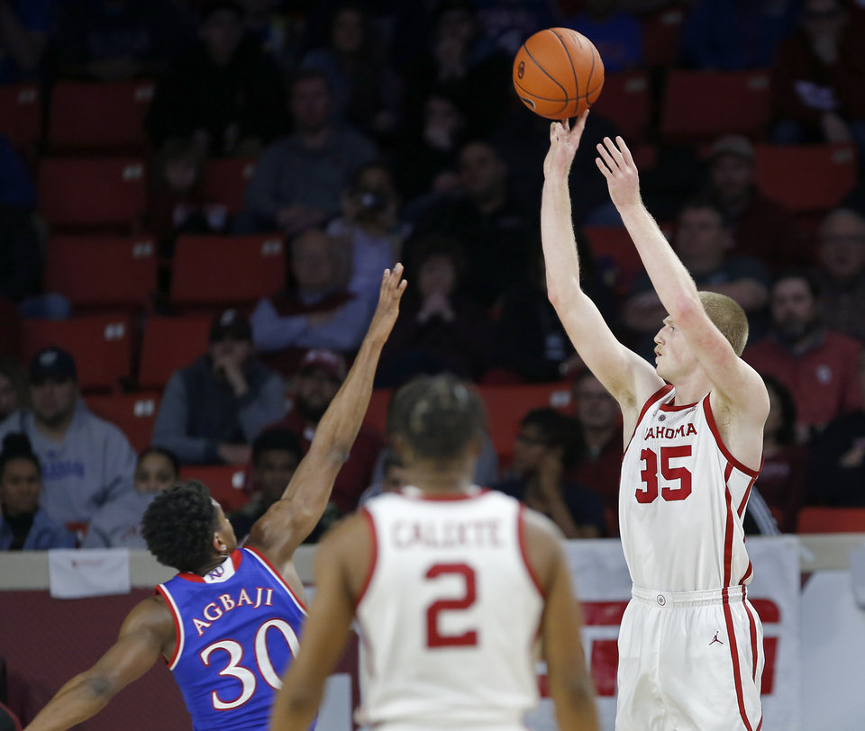 Photo - Oklahoma's Brady Manek (35) shoots a 3-point basket over Kansas's Ochai Agbaji (30) during the men's college basketball game between the University of Oklahoma and Kansas at the Lloyd Noble Center in Norman, Okla., Tuesday, March 5, 2019. Photo by Sarah Phipps, The Oklahoman