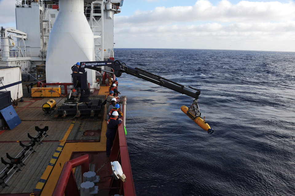 Photo - In a Monday, April 14, 2014 photo provided by the U.S. Navy, operators aboard the Australian defense vessel Ocean Shield move the U.S. Navy's Bluefin-21 autonomous underwater vehicle into position for deployment to search for the missing Malaysia Airlines Flight 370. On Tuesday, April 15, 2014, the U.S. Navy and search coordinators said that a built-in safety feature aborted what was supposed to have been a 16-hour mission to create a sonar map of the ocean floor after only six hours. (AP Photo/U.S. Navy, MC1 Peter D. Blair)