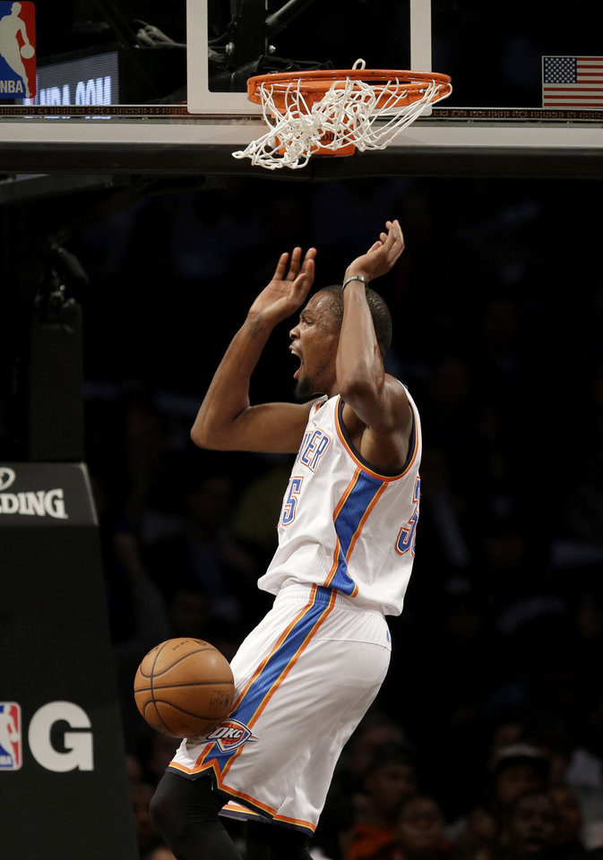 Photo - Oklahoma City Thunder's Kevin Durant reacts after dunking during the second half of an NBA basketball game against the Brooklyn Nets, Friday, Jan. 31, 2014, in New York. The Thunder defeated the Nets 120-95. (AP Photo/Seth Wenig)