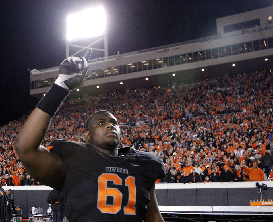 Photo - Former Oklahoma State Cowboy Michael Bowie (61) celebrates the Cowboys win over Kansas State during a college football game between the Oklahoma State University Cowboys (OSU) and the Kansas State University Wildcats (KSU) at Boone Pickens Stadium in Stillwater, Okla., Saturday, Nov. 5, 2011. Photo by Sarah Phipps, The Oklahoman