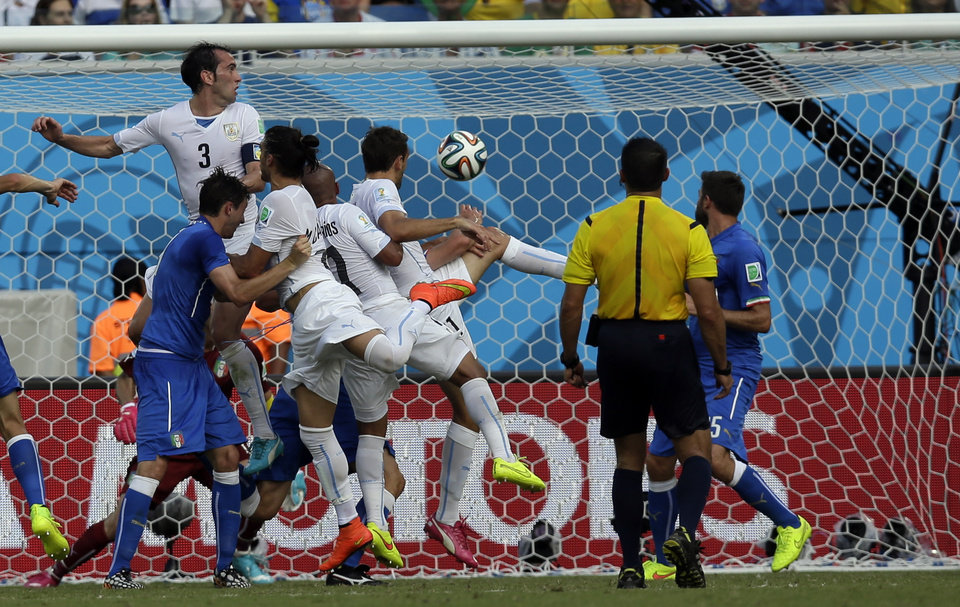 Photo - Uruguay's Diego Godin, left, scores the opening goal during the group D World Cup soccer match between Italy and Uruguay at the Arena das Dunas in Natal, Brazil, Tuesday, June 24, 2014. (AP Photo/Andrew Medichini)