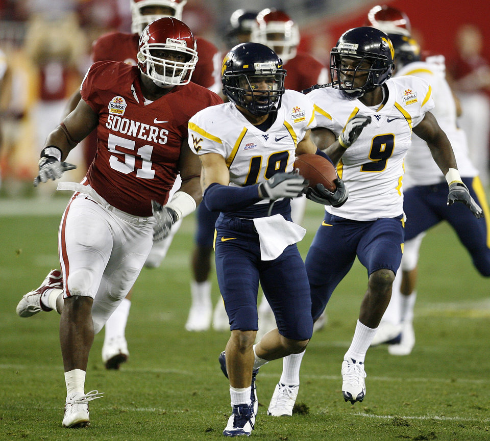 Photo - West Virginia's Vaughn Rivers (19) out runs Oklahoma's Demarrio Pleasant (51) on a kick return during the first half of the Fiesta Bowl college football game between the University of Oklahoma Sooners (OU) and the West Virginia University Mountaineers (WVU) at The University of Phoenix Stadium on Wednesday, Jan. 2, 2008, in Glendale, Ariz. 