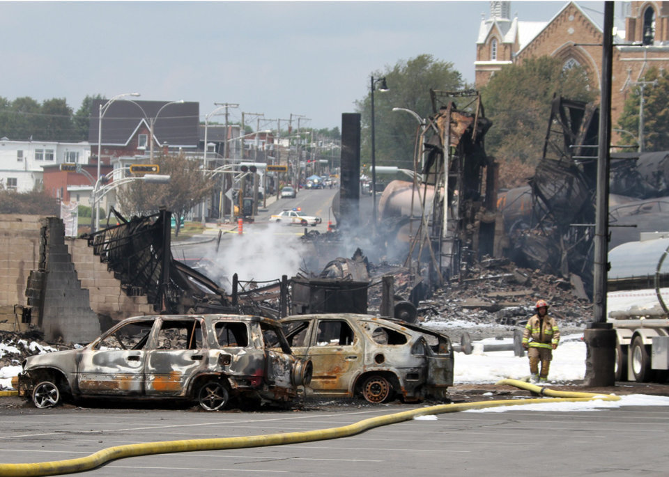 Photo - This photo provided by Surete du Quebec, shows wrecked oil tankers and debris from a runaway train on Monday, July 8, 2013 in Lac-Megantic, Quebec, Canada.  A runaway train derailed igniting tanker cars carrying crude oil early Saturday, July 6.  At least thirteen people were confirmed dead and nearly 40 others were still missing in a catastrophe that raised questions about the safety of transporting oil by rail instead of pipeline.  (AP Photo/Surete du Quebec, The Canadian Press)