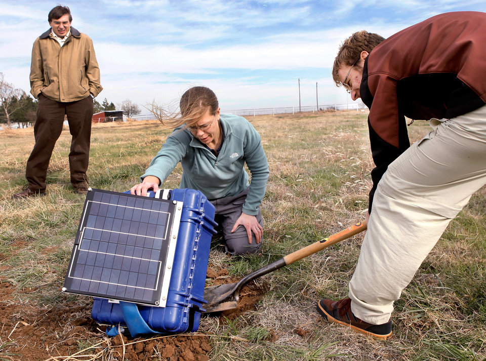 Photo - Graduate student Gabriel Mattei digs beneath a box held up by Katie Keranen, an assistant professor at the OU School of Geology and Geophysics,  as the two place a seismometer and this recording device into the ground on the property of Joseph and Mary Reneau Saturday afternoon, Nov. 5. , 2011.  The pair are accompanied by Austin Holland, left, a research seismologist with the Oklahoma Geological Survey.  They are placing the devices on the Reneau property after an earthquake rattled the area in the area in the early morning hours Saturday.  The Reneaus  were awakened around 2:15 a.m. when their house shook and items began falling off the walls and form shelves and cabinets inside their two-story brick ranch-style  home in rural Lincoln County, about  six miles northwest of Prague. Holland placed the quake's epicenter within two to three miles of the Reneau home.   Photo by Jim Beckel, The Oklahoman  ORG XMIT: KOD