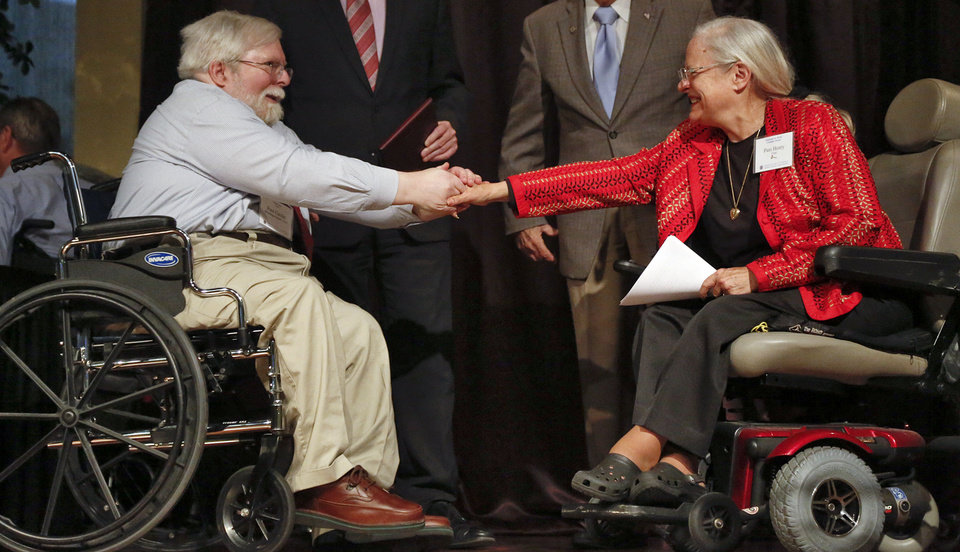 Photo - Paul Cardin shakes the hand of Pam Henry as he receives the George B. Lewis Advocacy Award Tuesday during the 23rd annual Mayor's Committee on Disability Concerns awards at St. Luke's United Methodist Church in Oklahoma City. Photo by Chris Landsberger, The Oklahoman  CHRIS LANDSBERGER