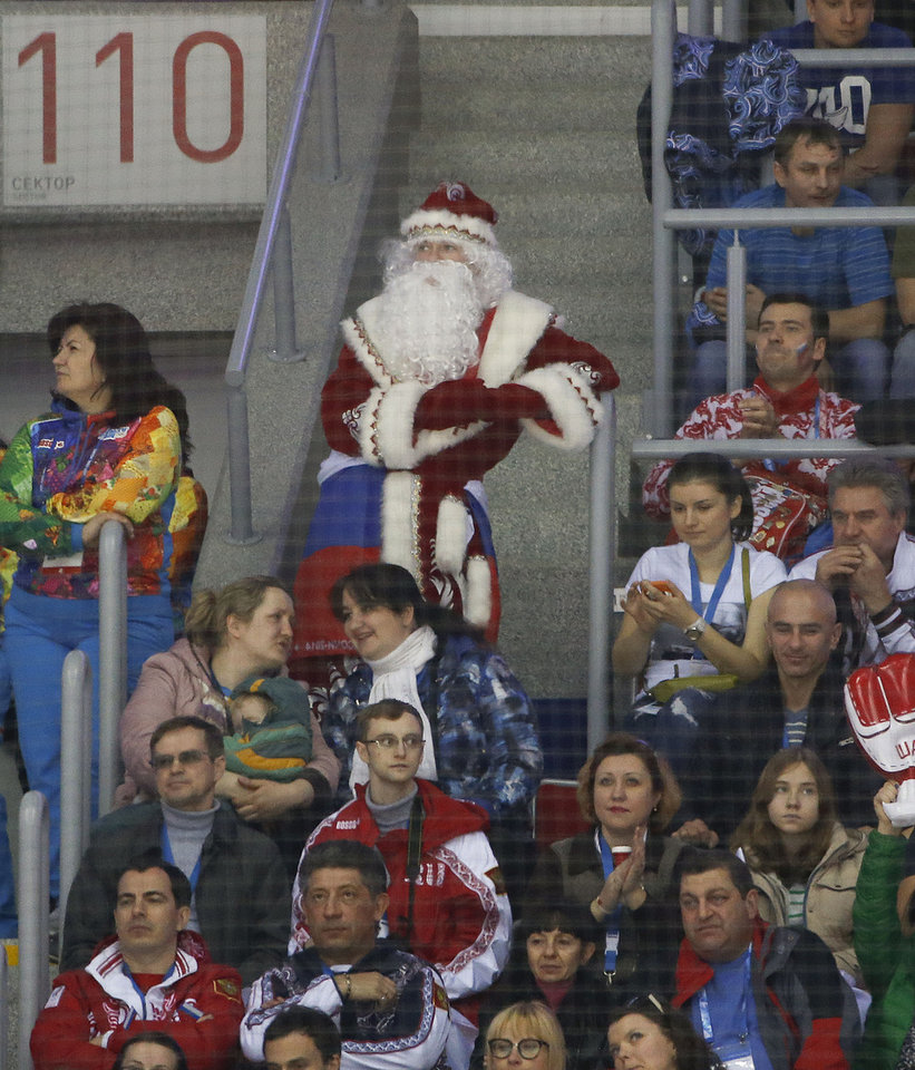 Photo - A hockey fan dressed as Grandfather Frost watches play between Russia and Slovenia in the first period of a men's ice hockey game at the 2014 Winter Olympics, Thursday, Feb. 13, 2014, in Sochi, Russia. (AP Photo/Julio Cortez)