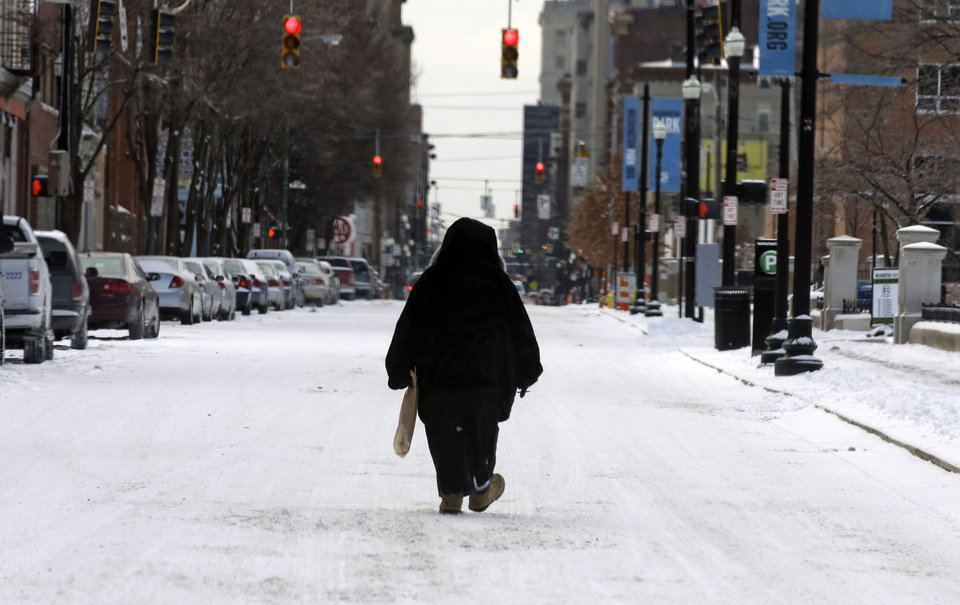 Photo - A pedestrian walks in the middle of a snow covered street, Monday, March 3, 2014, in downtown Cincinnati. The area received from three to six inches of new snow. (AP Photo/Al Behrman)