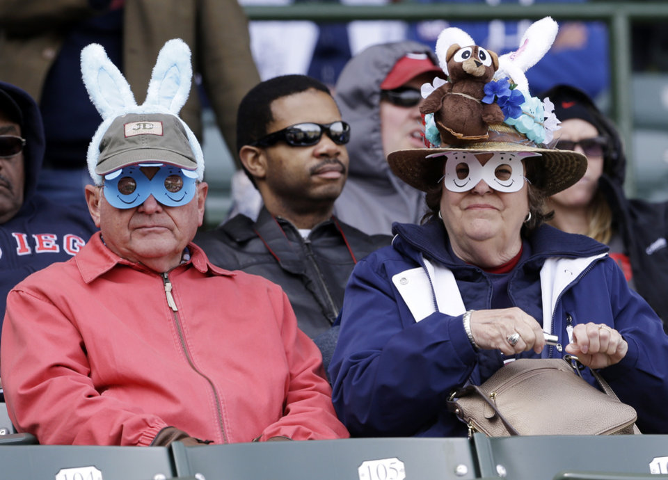 Photo - Baseball fans wearing Easter-related hats look to the field before a baseball game between the Cincinnati Reds and the Chicago Cubs in Chicago, Saturday, April 19, 2014. (AP Photo/Nam Y. Huh)