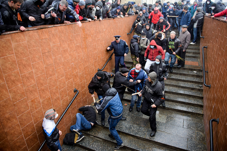 Photo - Pro-Russia supporters beat a pro-Western activist who lies on the stairs  during a pro Russian rally in Kharkiv, Ukraine, Sunday, April 13, 2014. Two rival rallies in Kharkiv turned violent after a group of pro-Russian protesters followed several pro-Ukrainian activists, beating them with baseball bats and sticks. (AP Photo/ Olga Ivashchenko)