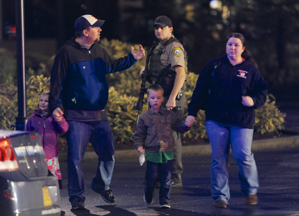 Photo - CORRECTS MALL LOCATION - A family leaves the scene of a multiple shooting at Clackamas Town Center Mall in Portland, Ore., Tuesday Dec. 11, 2012. A gunman is dead after opening fire in the Portland, Ore., shopping mall Tuesday, killing two people and wounding another, sheriff's deputies said. (AP Photo/Greg Wahl-Stephens)