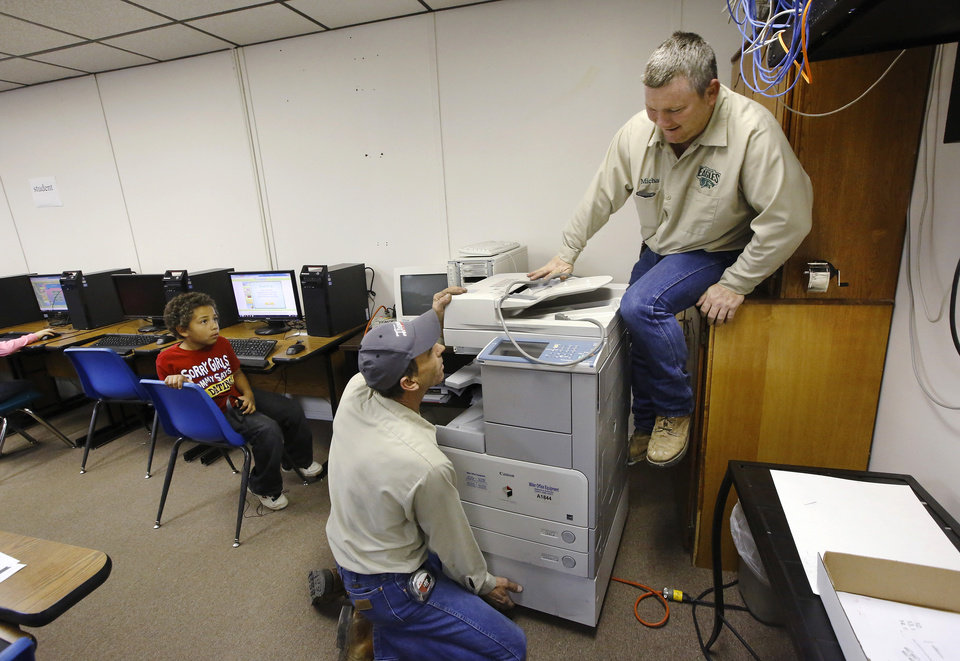 A Lane School maintenance worker climbs out of the small space in a corner of the computer room where he and a co-worker are putting a copy machine they brought from the closed Farris School. About 50 students transferred to Lane Public School after their former school, Farris School, was annexed by Lane in Atoka County.   Photo taken  March 1, 2013. Photo by Jim Beckel, The Oklahoman
