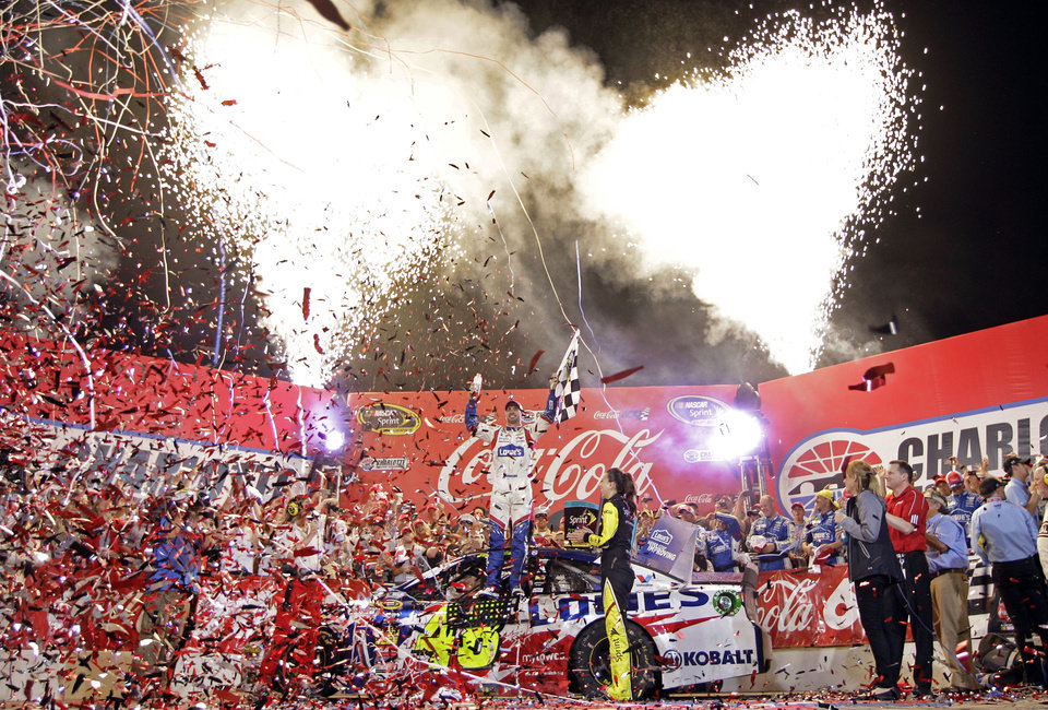 Photo - Driver Jimmie Johnsoon, center, celebrates in Victory Lane after winning the NASCAR Sprint Cup series Coca-Cola 600 auto race at Charlotte Motor Speedway, Sunday, May 25, 2014, in Concord, N.C. (AP Photo/Chuck Burton)