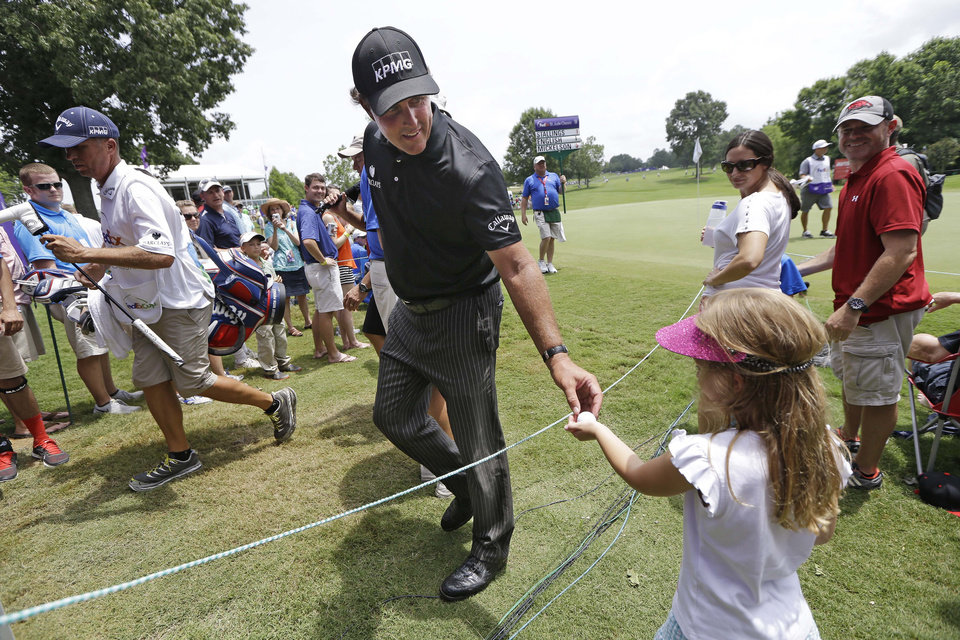 Photo - Phil Mickelson gives a golf ball to Taylor Hardin, 6, as he leaves the 17th green during the second round of the St. Jude Classic golf tournament Saturday, June 7, 2014, in Memphis, Tenn. Mickelson shot a par on the hole. Bad weather on Friday caused the second round to continue into Saturday. (AP Photo/Mark Humphrey)