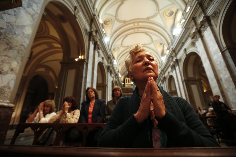 A woman prays inside the Metropolitan Cathedral in Buenos Aires, Argentina, early Wednesday, March 13, 2013. Argentine Jorge Bergoglio has been elected pope, the first ever from the Americas and the first from outside Europe in more than a millennium. He chose the name Pope Francis. (AP Photo/Victor R. Caivano) ORG XMIT: VC104