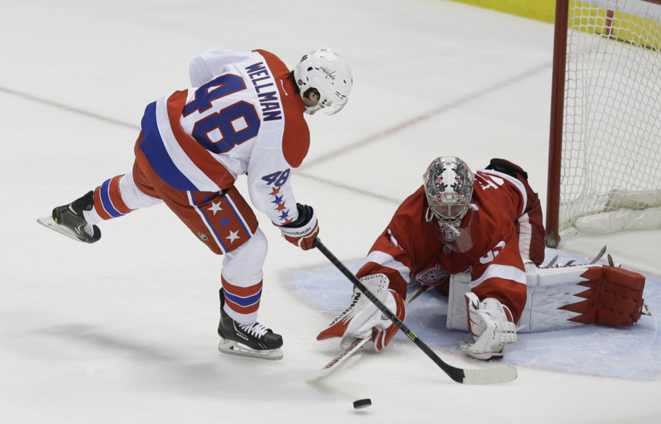 Photo - Detroit Red Wings goalie Jimmy Howard (35) deflects a shot by Washington Capitals center Casey Wellman (48) during the shootout of an NHL hockey game in Detroit, Friday, Jan. 31, 2014. The Red Wings won 4-3. (AP Photo/Carlos Osorio)
