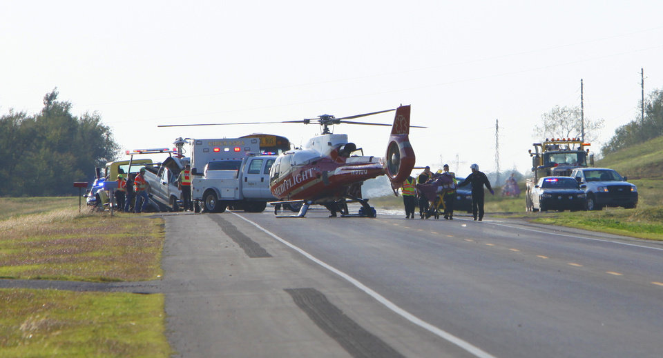 Photo - Mediflight crew transports the driver of a pickup truck that hit a Chickasha School bus on State Highway 62 east of Chickasha, Monday, October 15, 2012. The truck is being loaded on a wrecker on the left and the gurney with the victim is on the right. Photo By David McDaniel/The Oklahoman