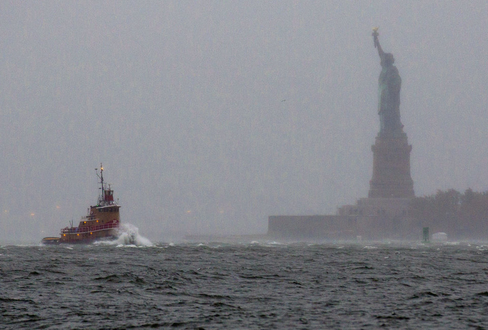 Photo - FILE - In a Monday, Oct. 29, 2012 file photo, waves crash over the bow of a tug boat as it passes near the Statue of Liberty in New York as rough water as the result of Hurricane Sandy churns the waters of New York Harbor. The Statue of Liberty survived Superstorm Sandy intact. But the storm flooded Liberty Island's power and heating systems and damaged its buildings. Superintendent David Luchsinger, who led reporters on a tour of Liberty Island on Friday, Nov. 30, 2012, says the National Park Service still does not know when the statue will reopen to the public or how much the island repairs will cost.  (AP Photo/Craig Ruttle, File)