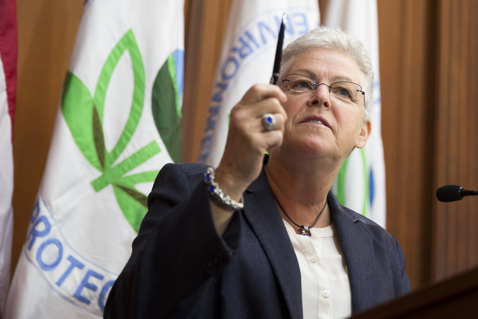Photo - Environmental Protection Agency (EPA) Administrator Gina McCarthy holds up a pen before signing new emission guidelines during an announcement of a plan to cut carbon dioxide emissions from power plants by 30 percent by 2030, Monday, June 2, 2014, at EPA headquarters in Washington.  In a sweeping initiative to curb pollutants blamed for global warming, the Obama administration unveiled a plan Monday that cuts carbon dioxide emissions from power plants by nearly a third over the next 15 years, but pushes the deadline for some states to comply until long after President Barack Obama leaves office. (AP Photo/ Evan Vucci)