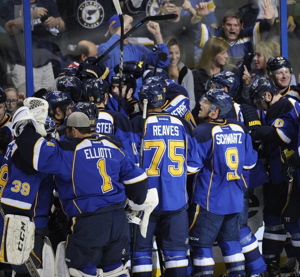 Photo - St. Louis Blues surround teammate Barret Jackman, center, after his game-winning goal against the Chicago Blackhawks during overtime in Game 2 of a first-round NHL hockey playoff series, Saturday, April 19, 2014, in St. Louis. (AP Photo/Bill Boyce)