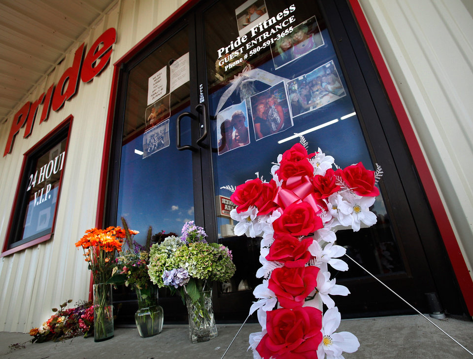 Photo - Flowers have been placed at the front door of the Dye's fitness center, Pride Fitness, in Elgin. Residents of Elgin Okla, react Tuesday, July 20, 2010, to yesterday's  shooting death of local teacher  Barbara Diane Dye at the hand of her husband,  Raymond Lee Dye, 42, in the parking lot of a bank in this southwest Oklahoma community of about 1400 people just north of Lawton.     