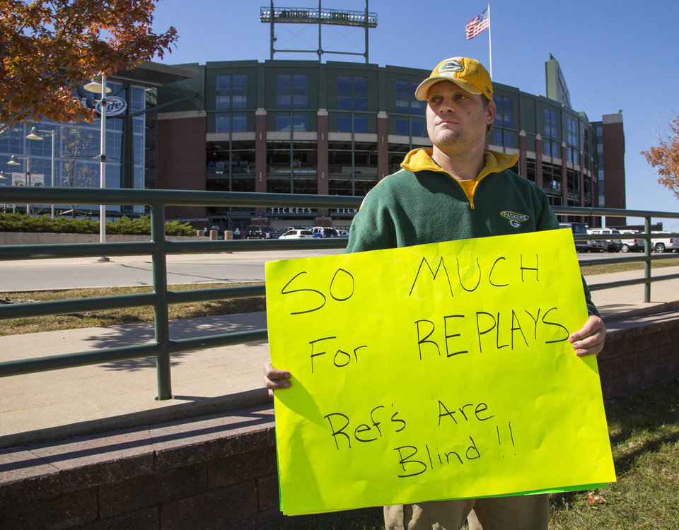 Photo -   Green Bay Packers fan Mike LePak holds a sign in front of Lambeau Field on Lombardi Avenue, Tuesday, Sept. 25, 2012, in Green Bay, Wis., in protest of a controversial call in the Packers 14-12 loss to the Seattle Seahawks, Monday night in Seattle. Just when it seemed that NFL coaches, players and fans couldn't get any angrier, along came a fiasco that trumped any of the complaints from the weekend. (AP Photo/Mike Roemer)