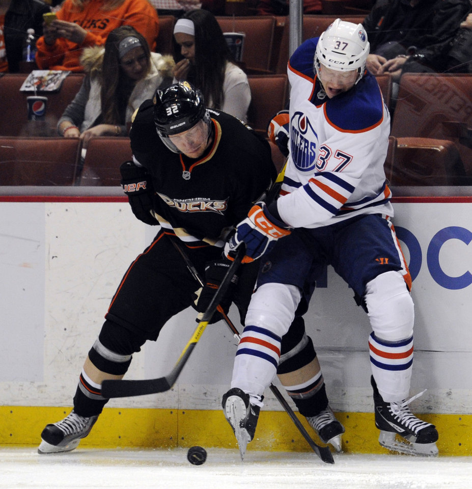 Photo -   Anaheim Ducks defenseman Toni Lydman (32), of Finland, and Edmonton Oilers center Lennart Petrell (37), of Finland, battle for the puck in the second period of an NHL hockey game in Anaheim, Calif., Monday, March 5, 2012. (AP Photo/Lori Shepler)