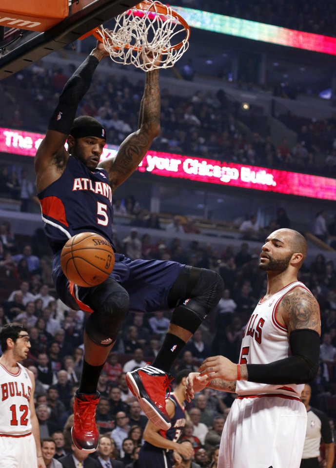 Photo - Atlanta Hawks forward Josh Smith (5) dunks in front of Chicago Bulls forward Carlos Boozer during the first half of an NBA basketball game Monday, Jan. 14, 2013, in Chicago. (AP Photo/Charles Rex Arbogast)