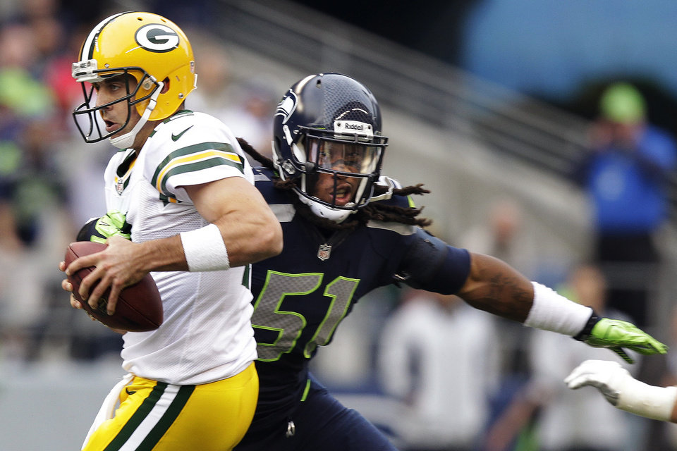 Photo -   Green Bay Packers quarterback Aaron Rodgers, left, is sacked by Seattle Seahawks defensive end Bruce Irvin (51) in the first half of an NFL football game, Monday, Sept. 24, 2012, in Seattle. (AP Photo/Stephen Brashear)