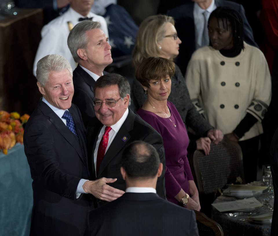 Former President Bill Clinton, left, greets Defense Secretary Leon Panetta, center, during a luncheon after the ceremonial swearing-in of President Barack Obama on Capitol Hill in Washington, Monday, Jan. 21, 2013. Others are House Majority Whip Rep. Kevin McCarthy, R-Calif., back left, and State Secretary Hillary Rodham Clinton.  (AP Photo/Manuel Balce Ceneta)