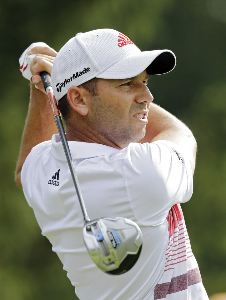 Photo - Sergio Garcia, from Spain, watches his drive on the fourth hole during the third round of the Bridgestone Invitational golf tournament Saturday, Aug. 2, 2014, at Firestone Country Club in Akron, Ohio. (AP Photo/Mark Duncan)