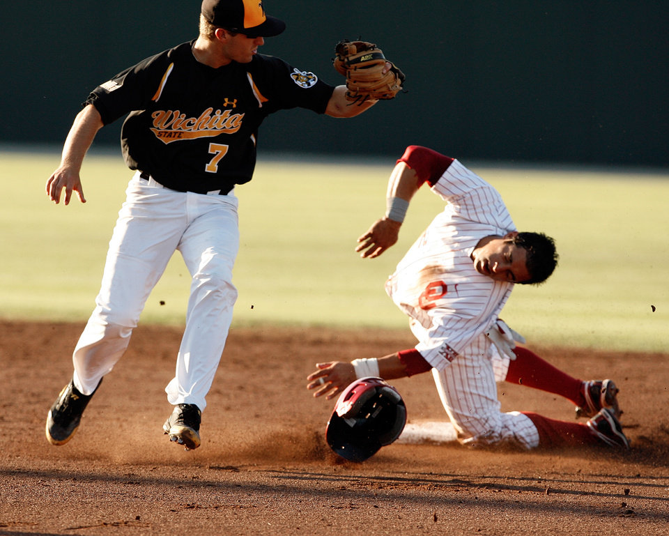 Photo - Bryant Hernandez is tagged out in the face by Taylor Brown as the University of Oklahoma plays Wichita State at L. Dale Mitchell Park in the NCAA Regional baseball tournament in Norman, Okla. on Friday, May 29, 2009. 