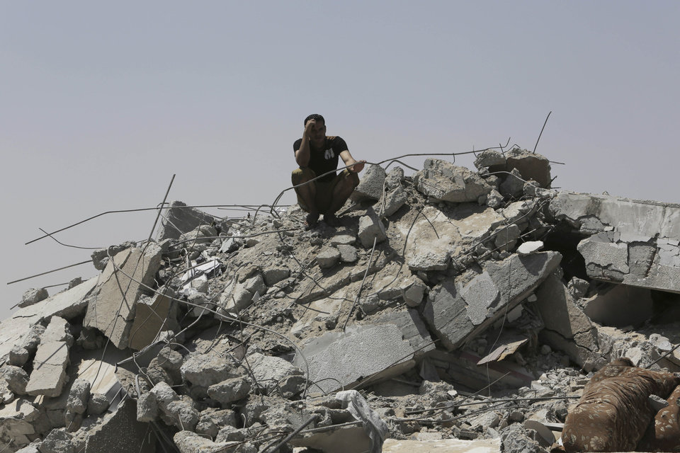 Photo - A Palestinian sits on the rubble of a destroyed house in the Bureij refugee camp in the central Gaza Strip, Friday, Aug. 1, 2014. (AP Photo/Adel Hana)