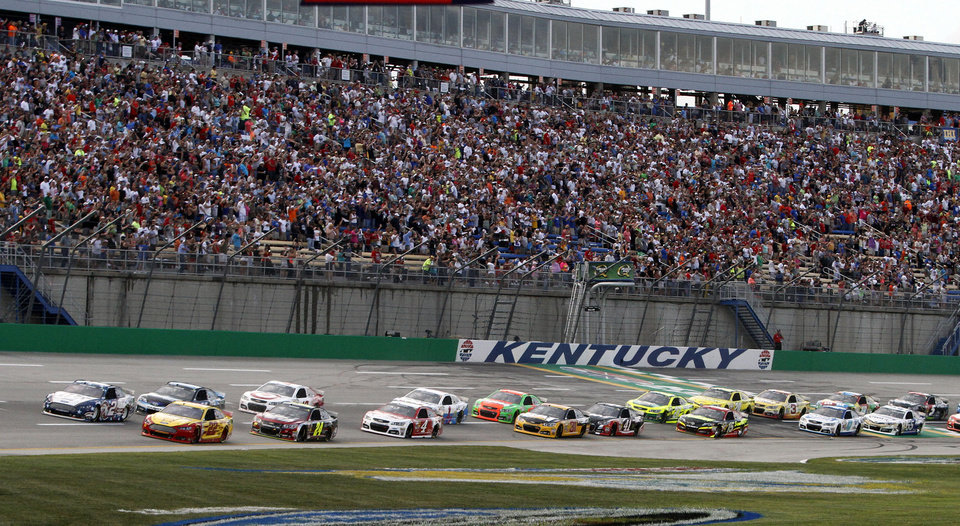 Photo - Brad Keselowski (2) leads the field across the line to start the NASCAR Sprint Cup series auto race Saturday, June  28, 2014, at Kentucky Speedway in Sparta, Ky. (AP Photo/James Crisp)
