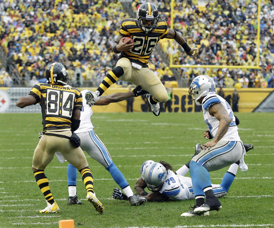 Photo - Pittsburgh Steelers running back Le'Veon Bell (26) leaps for more yardage as he tries to evade Detroit Lions strong safety Glover Quin (27) and the defense in the first half of an NFL football game in Pittsburgh, Sunday, Nov. 17, 2013. (AP Photo/Gene J. Puskar)