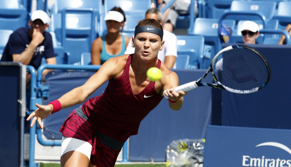 Photo - Lucie Safarova, from Czech Republic, returns to Venus Williams during a first round match at the Western & Southern Open tennis tournament, Tuesday, Aug. 12, 2014, in Mason, Ohio. (AP Photo/David Kohl)
